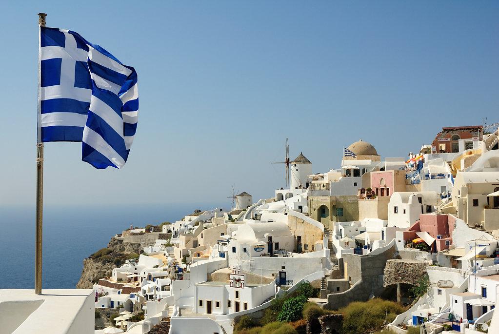 The flag and the Greek windmills - Santorini, Greece